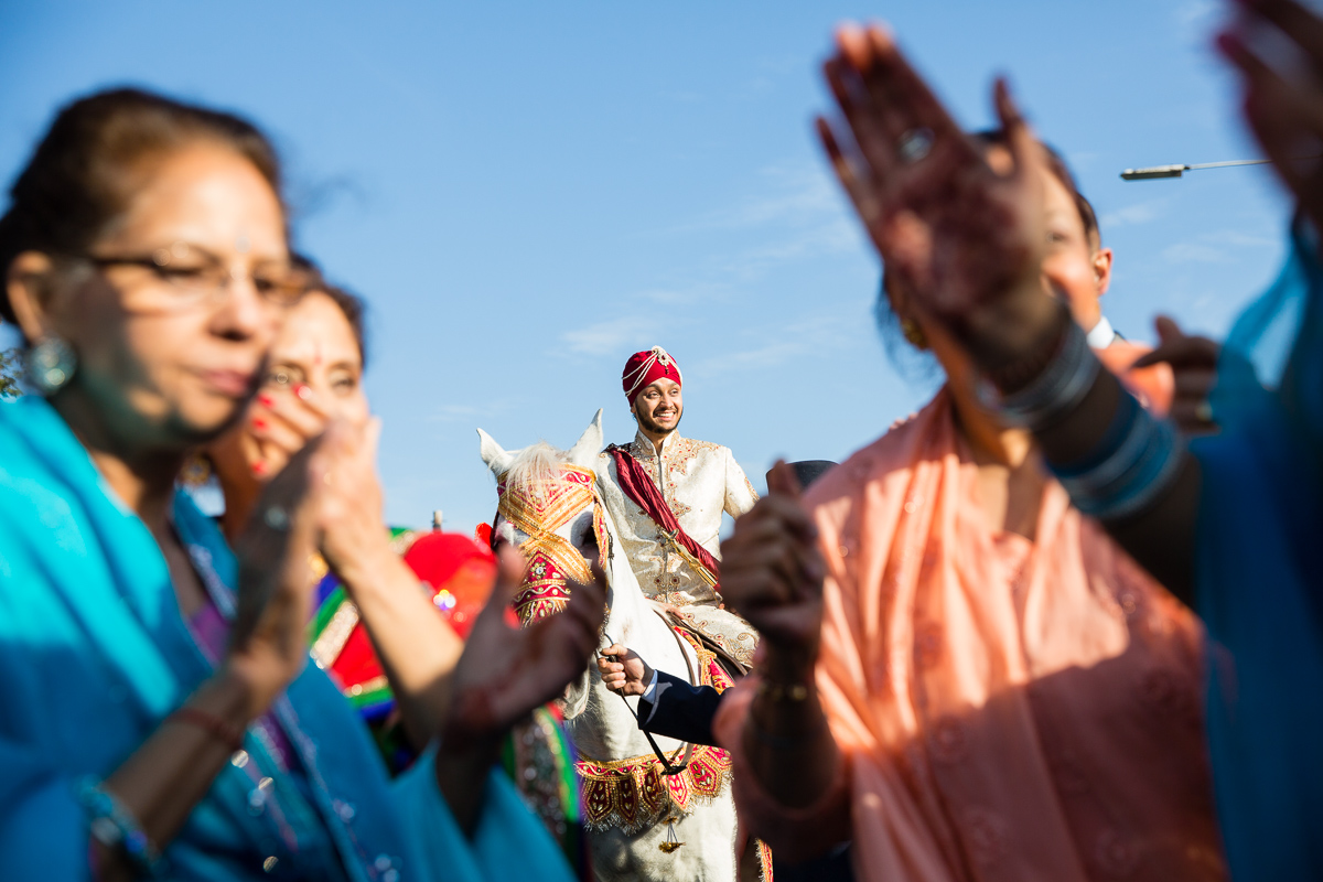 Sikh wedding photography - groom arrives on horse