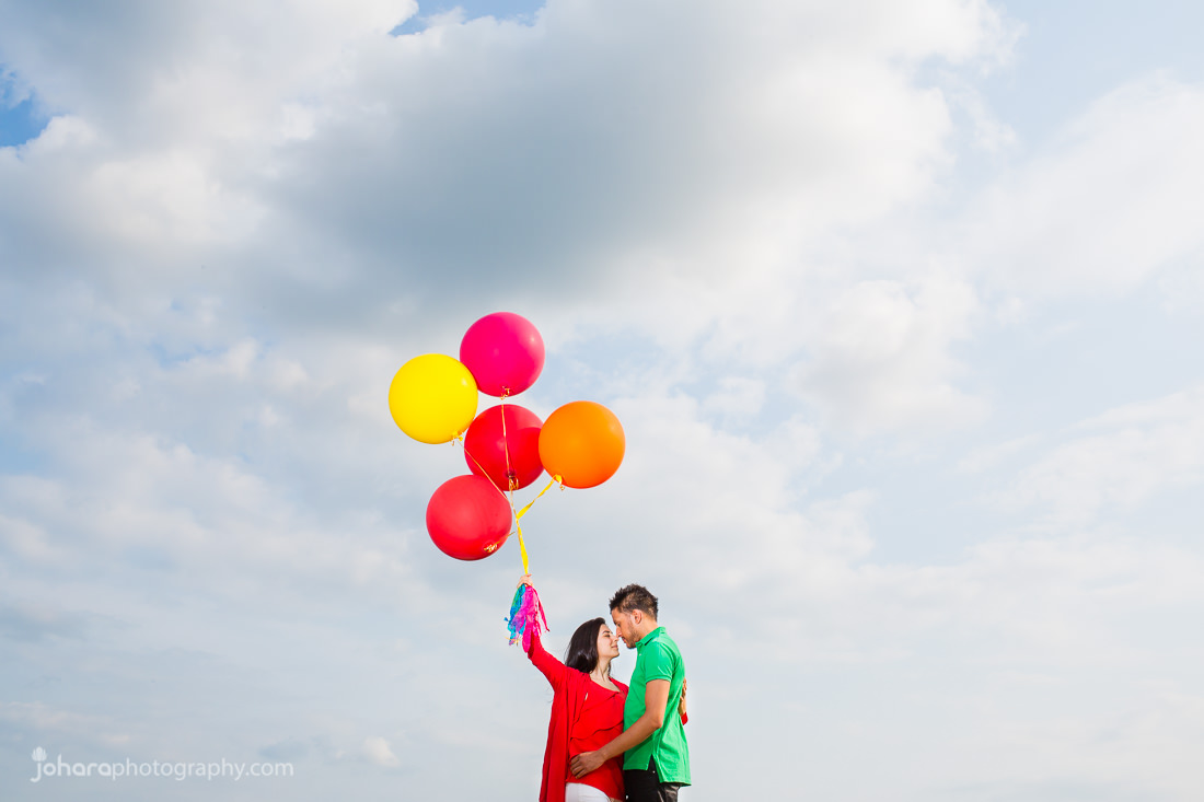 Couple (Mitikia and Gurpreet) holding each other with bride holding coloured balloons in the clouds