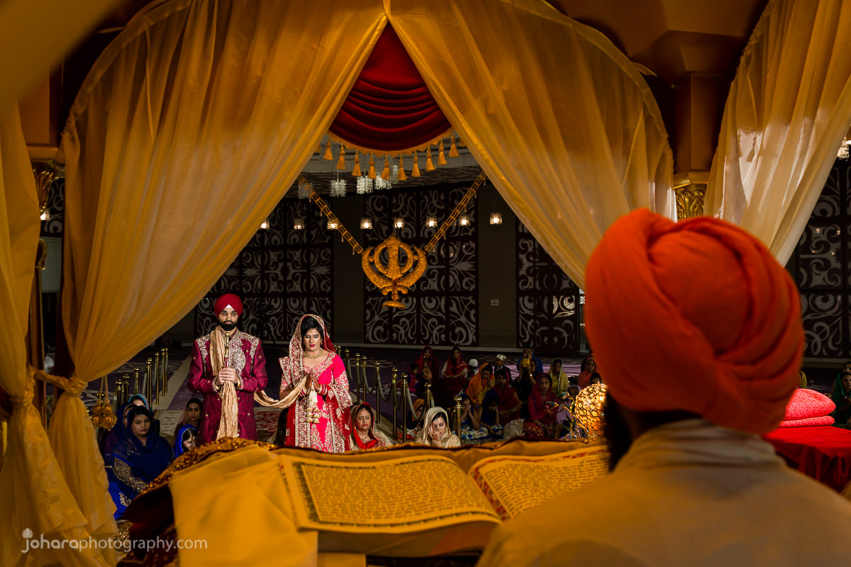 Sikh wedding ceremony, photo of bride and groom from behind the priest